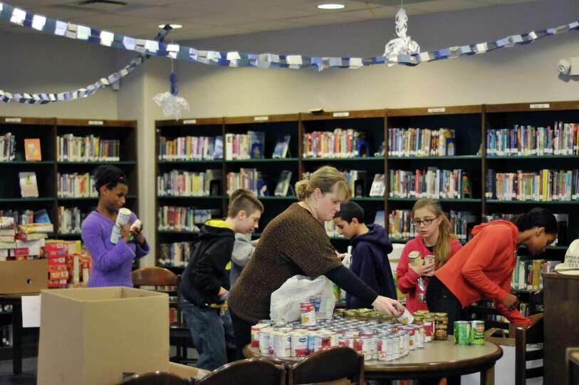 Students and staff sort through donated food at Knickerbacker Middle School on Wednesday, Dec. 17, 2