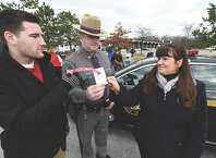 Northway crash victim Matt Hardy, left  joins with NYSP Troop T member Mathew Izbicki, center and Michele Fonda of Mother Against Drunk Driving to kick off MADD's 28th Annual Red Ribbon Campaign on Friday, December 26. To mark the annual campaign aimed at preventing drunk driving, Thruway Authority toll collectors will hand out red ribbons at select toll facilities along the Thruway.    (Skip Dickstein/Times Union)