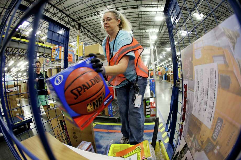 In this Dec. 1, 2014 photo, Teresa Clark fills an order at the Amazon fulfillment center on Cyber Monday, in Lebanon, Tenn. Retailers have been pushing back shipping deadlines and extending free shipping offers, putting more pressure package carriers. Amazon extended its free-shipping deadline by one day to Dec. 19. (AP Photo/Mark Humphrey) ORG XMIT: NYBZ170 Photo: Mark Humphrey / AP