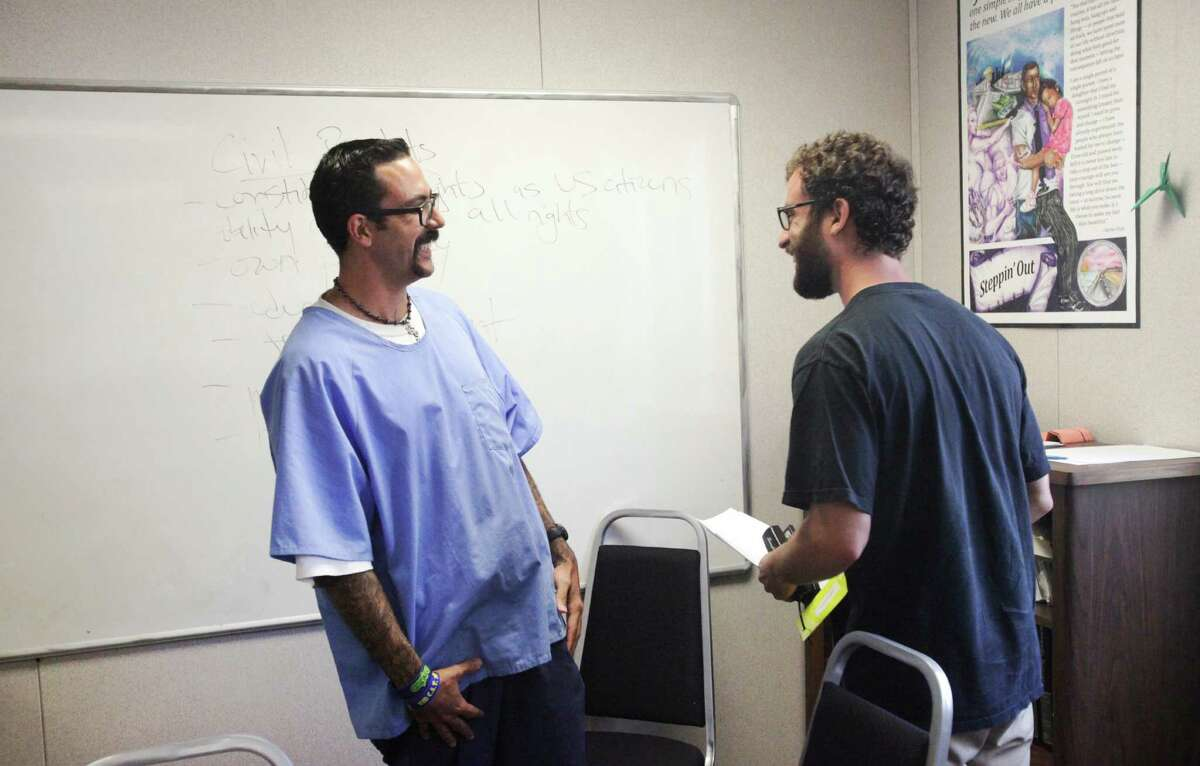 San Quentin inmate Tommy Winfrey, 36 (left), chats with his history teacher, Jake Martin Grumbach, after class.