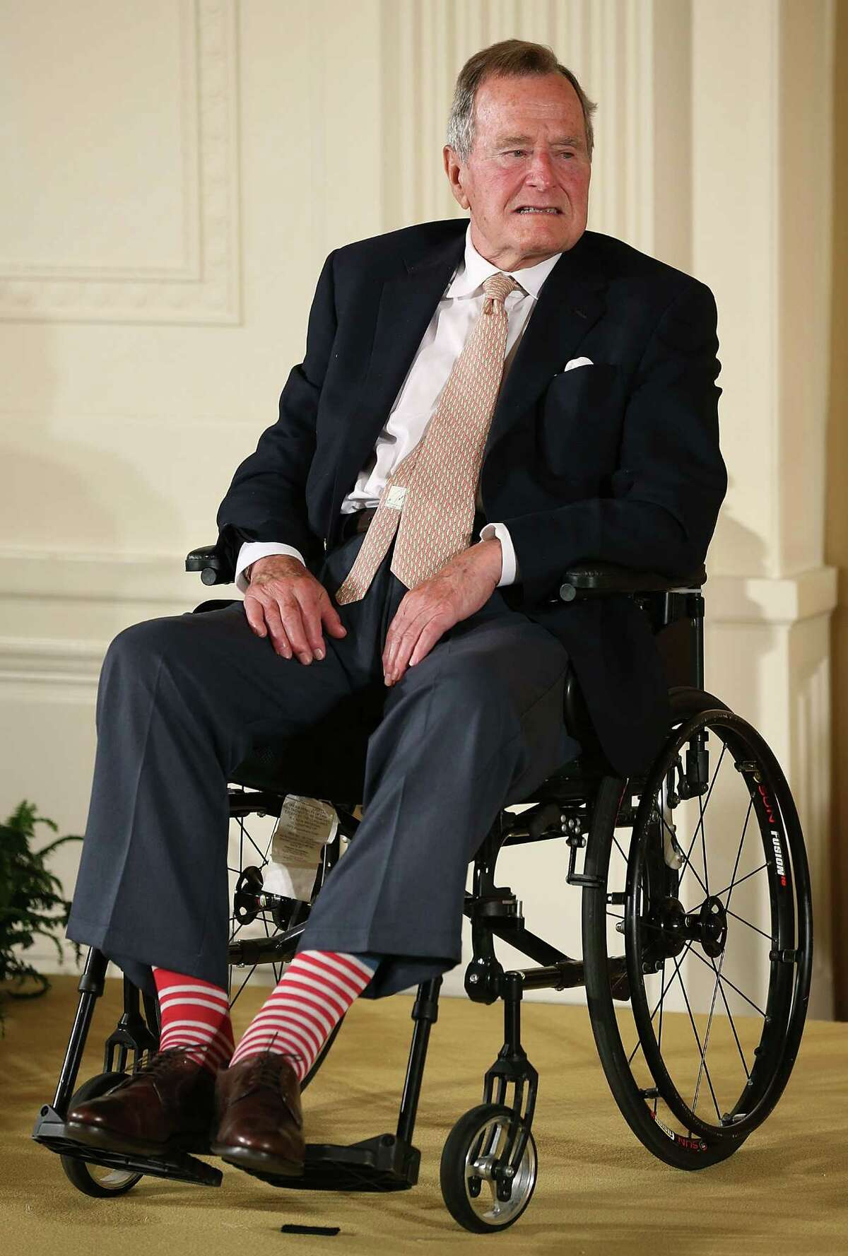 FILE - DECEMBER 24, 2014: It was reported that former U.S. President George H.W. Bush was hospitalized after experiencing a shortness of breath December 24, 2014 in Houston, Texas. WASHINGTON, DC - JULY 15: Former President George H. W. Bush wears red stripped socks as he sits in a wheelchair during an event in the East Room at the White House, July 15, 2013 in Washington, DC. Bush joined President Obama in hosting the event to honor the 5,000th Daily Point of Light Award winner. (Photo by Mark Wilson/Getty Images)