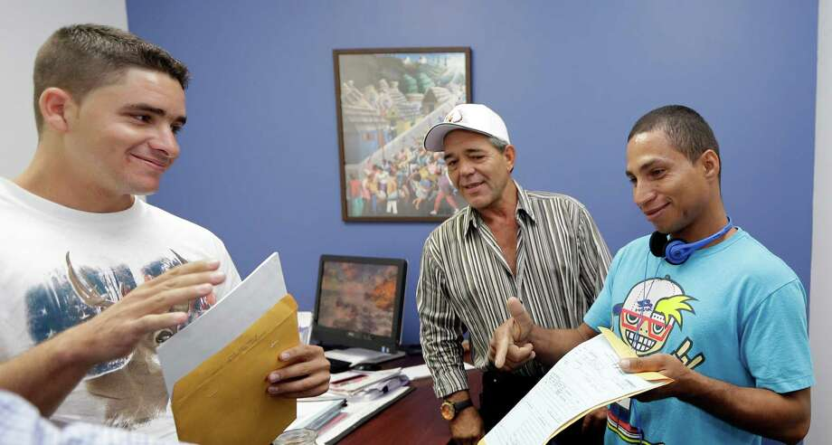 """ADVANCE FOR SATURDAY DEC. 27, 2014 In this photo taken Tuesday, Oct. 28, 2014, Jose Fuente Lastre, left, Antonio Cardenas, center, and Yanier Martinez Diaz, right, open their Immigration documents at the Church World Service office in Miami. One month and three days later after their arrival, the men woke before dawn and gathered five big duffel bags and four smaller ones, filled with donated clothes. They left for Portland, Oregon, where Church World Service had arranged housing, English classes, and jobs. Cardenas proudly took photos on his cell phone: Lastre holding up his airplane ticket; Diaz pushing a cart of luggage. Diaz and Lastre had never been on a plane before. None spoke English. But they had survived much worse. """"The biggest scare is over,"""" Cardenas said. (AP Photo/Alan Diaz) ORG XMIT: FLAD207 Photo: Alan Diaz / AP"""