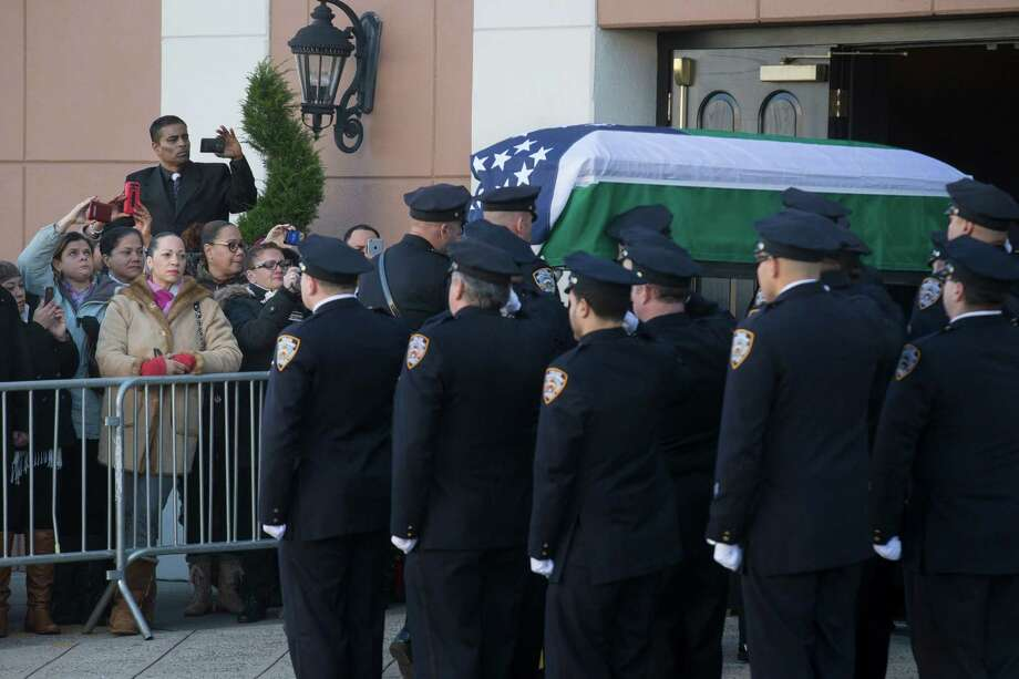 The casket of New York Police Department officer Rafael Ramos arrives to his wake at Christ Tabernacle Church in the Glendale section of Queens, where he was member, Friday, Dec. 26, 2014, in New York. Ramos was killed Dec. 20 along with his partner, Officer Wenjian Liu, as they sat in their patrol car on a Brooklyn street. The shooter, Ismaaiyl Brinsley, later killed himself. (AP Photo/John Minchillo) ORG XMIT: NYJM105 Photo: John Minchillo / FR170537 AP