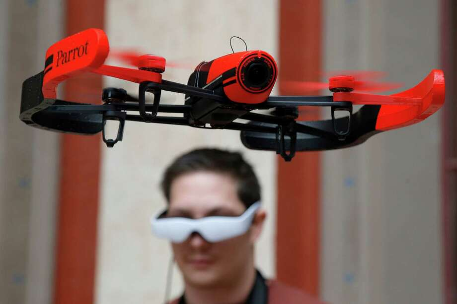 """FILE - In this Nov. 7, 2014 file photo, pilot Maxime Tran Quan Tien guides his Parrot Bebop drone during a presentation to the press in Paris. Drones _ the remotely controlled flying devices that often carry cameras and can be navigated with a smartphone or controller _ are """"taking off"""" as popular gifts this year, for serious hobbyists and casual users alike, young and old. Photo: Francois Mori, AP / AP"""