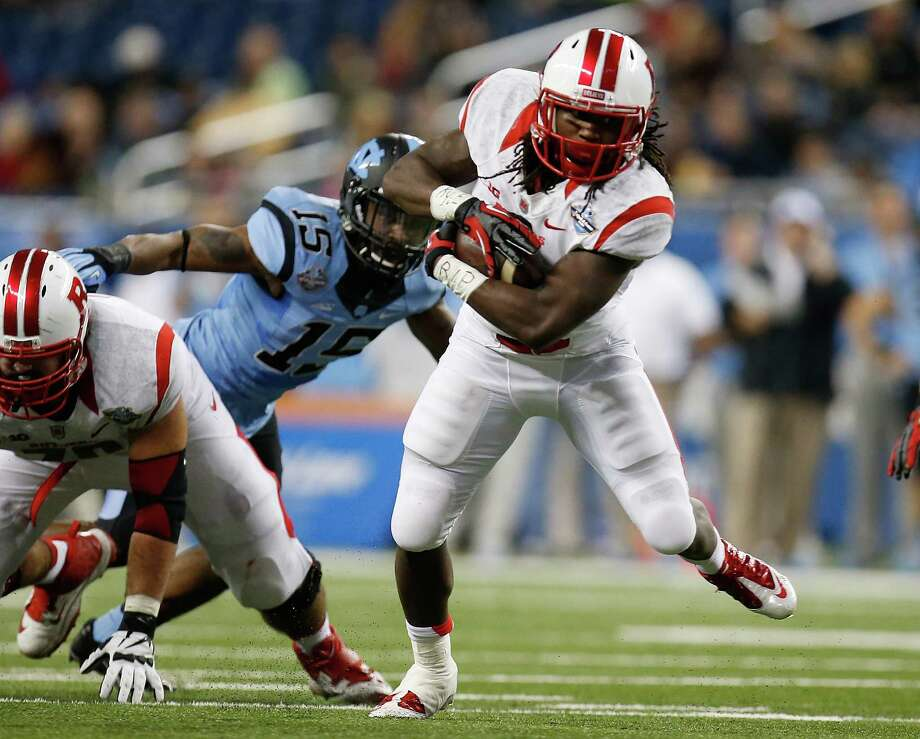DETROIT, MI - DECEMBER 26: Josh Hicks #8 of the Rutgers Scarlet Knights runs for a second quarter touchdown after avoiding the tackle of Donnie Miles #15 of the North Carolina Tar Heels during the Quick Lane Bowl at Ford Field on December 26, 2014 in Detroit Michigan. (Photo by Gregory Shamus/Getty Images) ORG XMIT: 528871617 Photo: Gregory Shamus / 2014 Getty Images