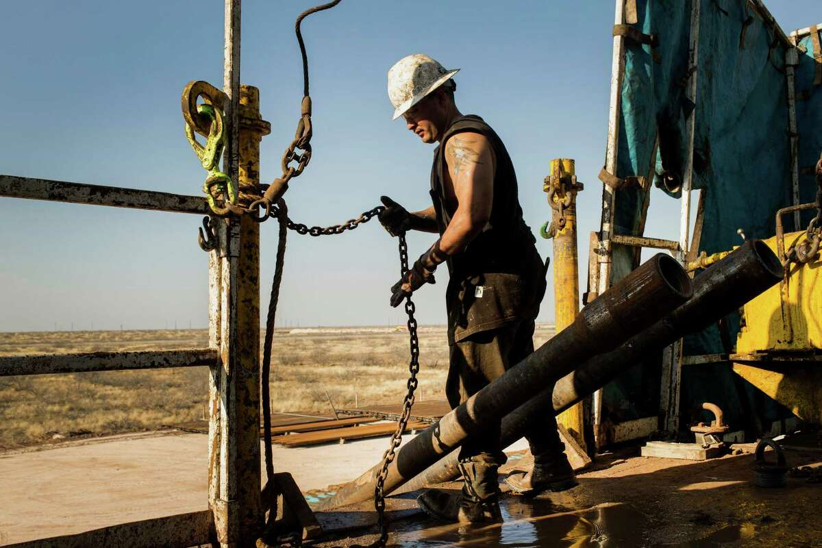 A worker prepares to lift drills by pulley to the main floor of Endeavor Energy Resources LP's Big Dog Drilling Rig 22 in the Permian basin outside of Midland, Texas, U.S., on Friday, Dec. 12, 2014. Photographer: Brittany Sowacke/Bloomberg