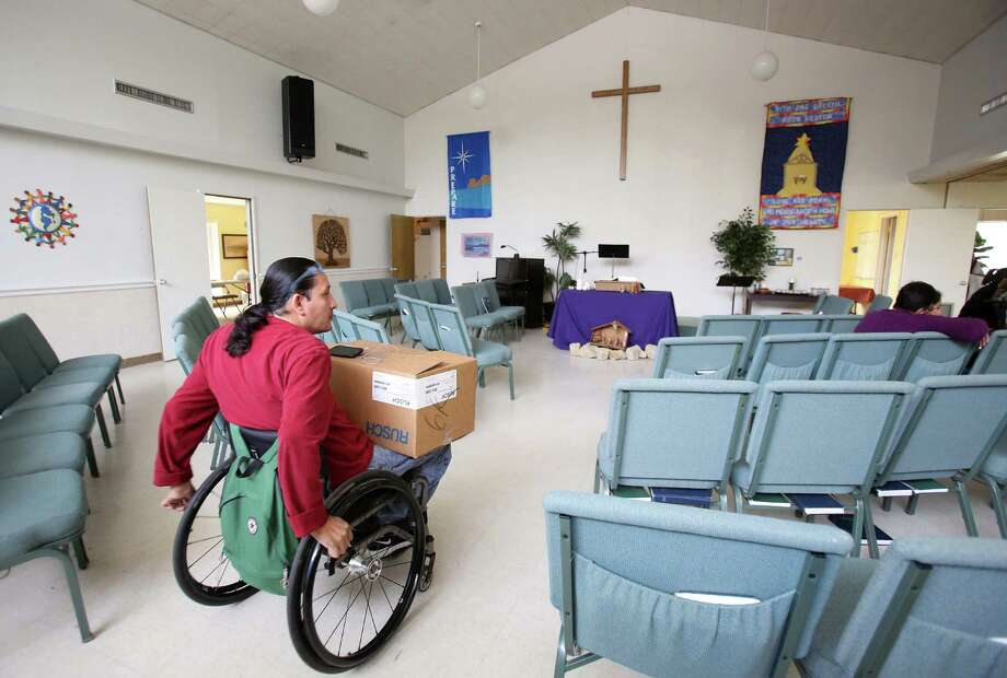 Juan Rodriguez returns to a group discussion after receiving medical supplies from Living Hope Wheelchair Association.  Living Hope Wheelchair Association was formed in 2005, after Harris County Hospital District decided to stop providing necessary medical supplies to people with spinal cord injuries who were not eligible for Medicaid -- most of them undocumented immigrants. Photo: Mayra Beltran, Houston Chronicle / © 2014 Houston Chronicle