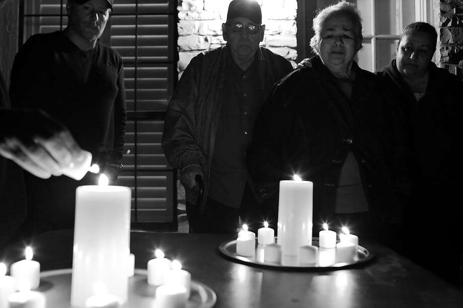 Tom Freed (from left), Hector Garcia Sr., Elena Garcia and Rosie Garcia watch as each family member lights a candle for Hector Garcia Jr. and his sister, Terry Amen, on Christmas Eve, their first holiday without Garcia. Photo: Lisa Krantz /San Antonio Express-News / San Antonio Express-News