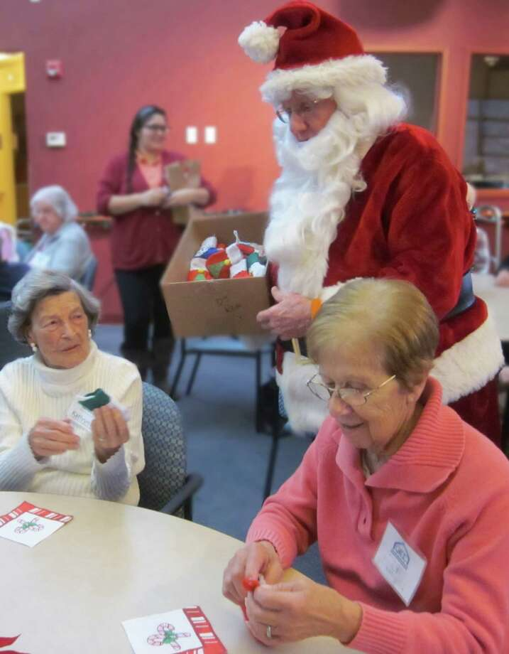 Santa hands out treats to River House members at the Adult Day Center's annual holiday celebration. The party kicked off with a performance of traditional carols by the River House Bell Choir, followed by a reading from ìíTwas the Night Before Christmas,î and a musical performance. Photo: Contributed Photo / Greenwich Citizen