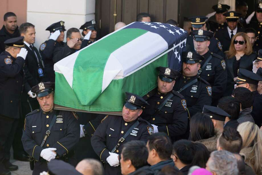 NEW YORK, NY - DECEMBER 27:  Pallbearers carry the casket for the funeral of slain New York Police Department (NYPD) officer Rafael Ramos at the Christ Tabernacle Church on December 27, 2014 in the Glenwood section of the Queens borough of New York City. Ramos was shot, along with Police Officer Wenjian Liu while sitting in their patrol car in an ambush attack in Brooklyn on December 20. Thousands of fellow officers, family, friends and Vice President Joseph Biden arrived at the church for the funeral. Photo: Kevin Hagen, Getty Images / 2014 Getty Images