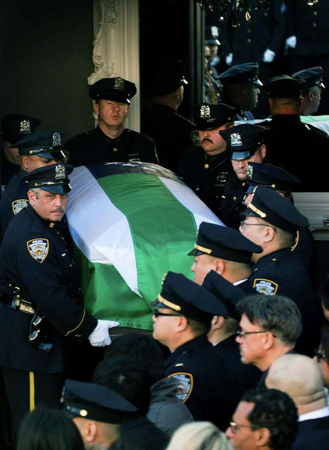 NEW YORK, NY - DECEMBER 27:  Pallbearers carry the casket during the funeral of slain New York Police Department (NYPD) officer Rafael Ramos at the Christ Tabernacle Church on December 27, 2014 in the Glenwood section of the Queens borough of New York City. Ramos was shot, along with Police Officer Wenjian Liu while sitting in their patrol car in an ambush attack in Brooklyn on December 20. Thousands of fellow officers, family, friends and Vice President Joseph Biden arrived at the church for the funeral. Photo: Kevin Hagen, Getty Images / 2014 Getty Images