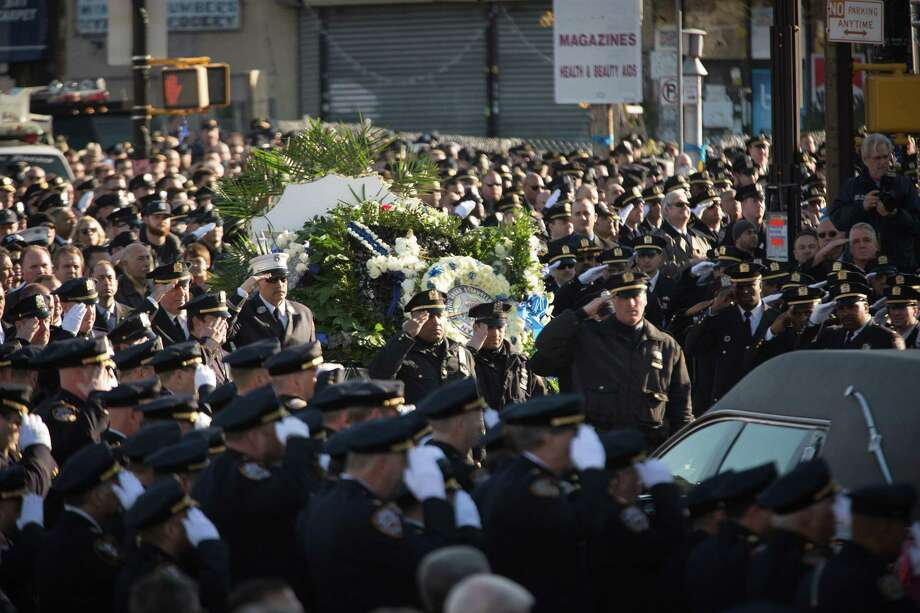 NEW YORK, NY - DECEMBER 27:  Officers salute outside the church following the funeral of slain NYPD officer Rafael Ramos at the Christ Tabernacle Church in the Glenwood section of Queens, NY. Ramos was shot, with his partner Police Officer Wenjian Liu, last Saturday while sitting in their police car. Photo: Kevin Hagen, Getty Images / 2014 Getty Images