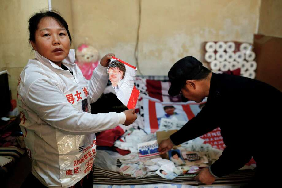 Zhang Xiuhong holds a poster of her missing daughter that she says was ripped by police. Photo: Andy Wong / Associated Press / AP
