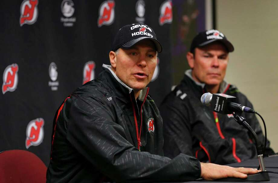 Former New Jersey assistant Scott Stevens (left) and former Washington head coach Adam Oates talk to reporters after agreeing to take over as co-coaches of the Devils. Photo: Adam Hunger / Associated Press / FR110666 AP