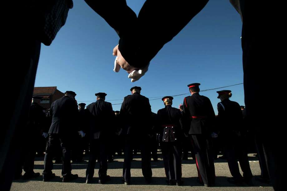 Police officers hold hands in prayer during the funeral service of New York City police officer Rafael Ramos in the Glendale section of Queens, Saturday, Dec. 27, 2014, in New York. Ramos and his partner, officer Wenjian Liu, were killed Dec. 20 as they sat in their patrol car on a Brooklyn street. The shooter, Ismaaiyl Brinsley, later killed himself. (AP Photo/John Minchillo) Photo: John Minchillo / Associated Press / FR170537 AP