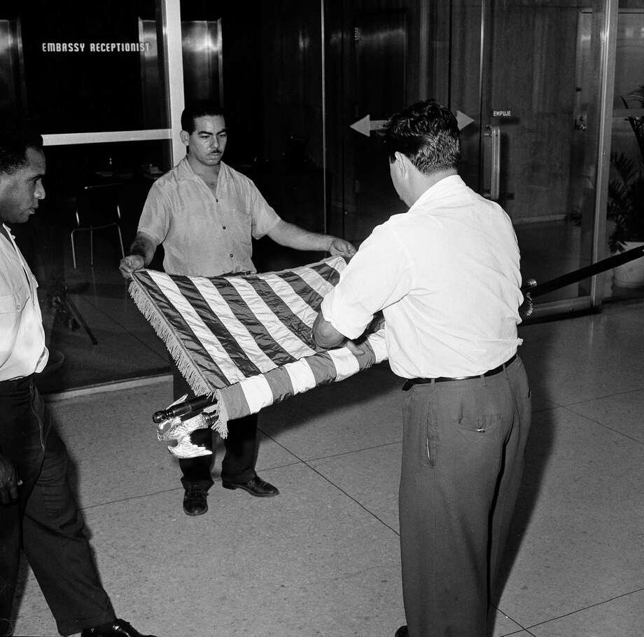 FILE - This Jan. 7, 1961 file photo shows unidentified U.S. embassy employees rolling up a U.S. flag as the embassy transfers American affairs to the Swiss government, in Havana, Cuba. The U.S. Interests Section is poised to be transformed into a full embassy, which would include such symbolic measures such as raising the American flag on the Malecon, after the U.S. and Cuba announced on Dec. 17, 2014 they are re-establishing full diplomatic relations. (AP Photo, File) Photo: Anonymous / Associated Press / AP