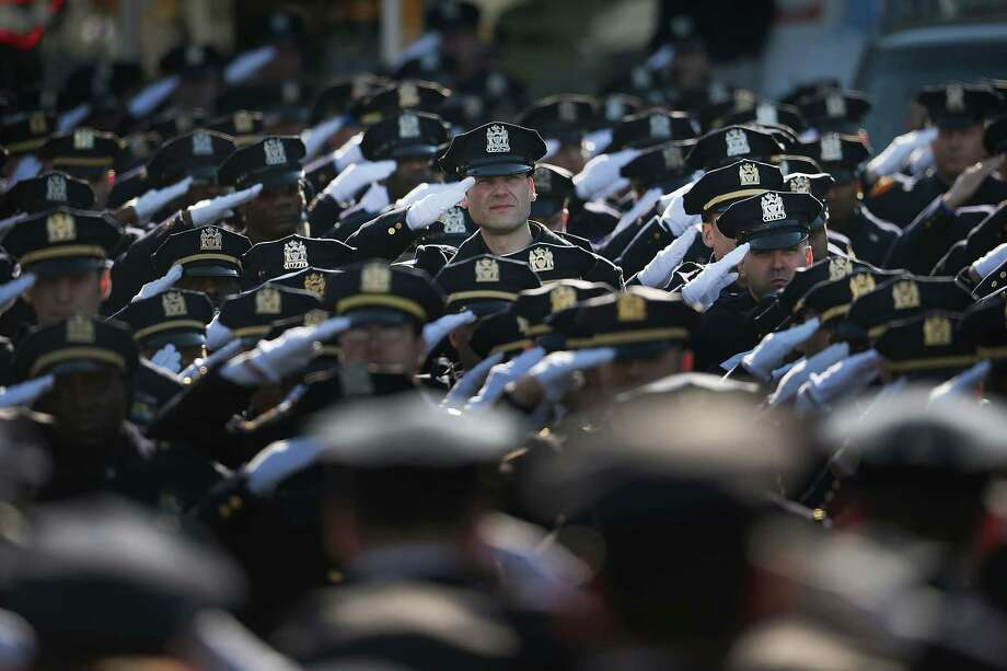NEW YORK, NY - DECEMBER 27:  Police officers from around the country salute outside of Christ Tabernacle Church for the funeral of slain New York City Police Officer Rafael Ramos, one of two officers murdered while sitting in their patrol car in an ambush in Brooklyn last Saturday afternoon on December 27, 2014 in New York City. Thousands of fellow officers, family, friends and Vice President Joseph Biden are expected at the church in the Glendale neighborhood of Queens for the funeral.  (Photo by Spencer Platt/Getty Images) ORG XMIT: 530024513 Photo: Spencer Platt / 2014 Getty Images