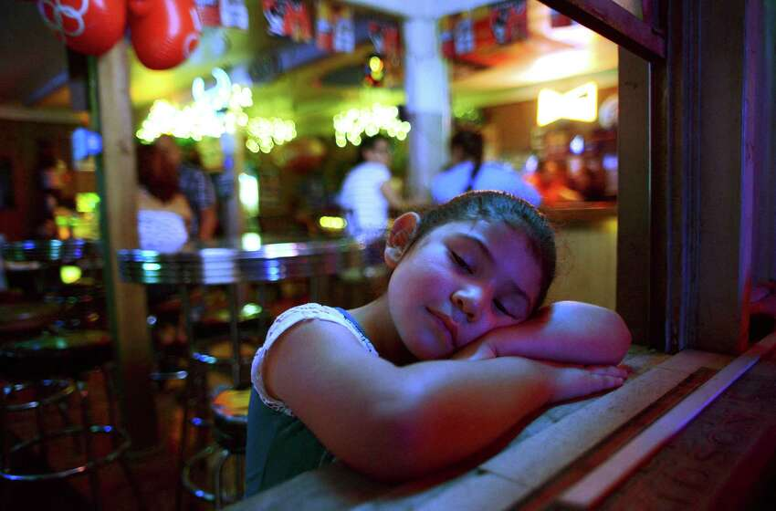 Courtney Carreon relaxes as her mother, Michelle Hernandez, tends bar at Hernandez Ice House on West Mitchell on Saturday, Aug. 16, 2014.