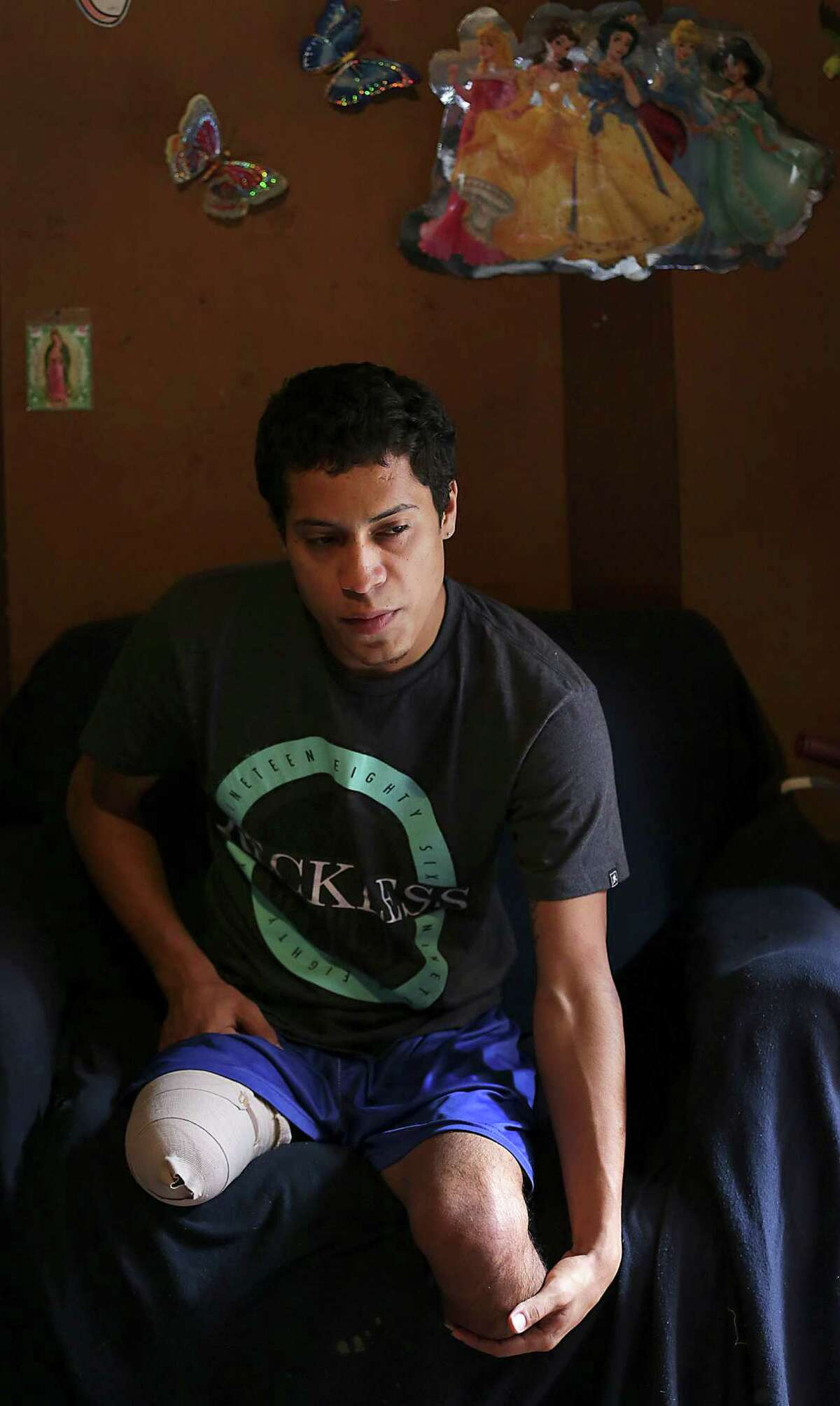 """Marco Oliva, 21, rubs in leg in his home in Tegucigalpa. Oliva had his legs amputated after trying to jump on a train heading north through Mexico earlier this year. He lives in a house in Barrio Colonia Divanna dominated by the gang """"18"""", in Tegucigalpa, Honduras, Friday, July 4, 2014. His father was killed by gang members in 1995, when he was 2 yrs old."""