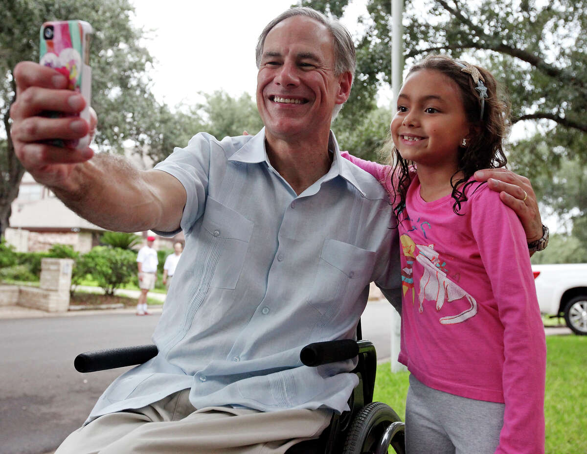 Texas Attorney General Greg Abbott poses for a selfie with Ali Gorena, 7, during a block walk in the 1000 block of South Peking Street Saturday Sept. 20, 2014 in McAllen, Tx.