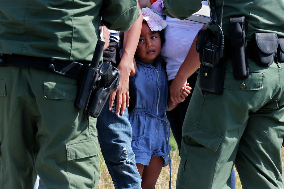 U.S. Border Patrol agents question a group of adult and minor immigrants near Anzalduas Park, southwest of McAllen, Texas, Wednesday, June 11, 2014. A wave of Central American adults with children and unaccompanied minors has overwhelmed U.S. Immigration and Customs detention centers. Immigration officials release some of them on their own recognizance after undergoing processing. Photo: Jerry Lara, By Jerry Lara, San Antonio Express_News / ©2014 San Antonio Express-News