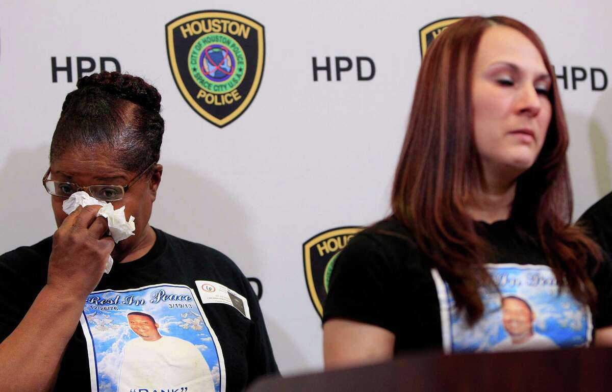 Linda Johnson, mother of shooting victim Dameon Johnson, wipes tears as family friend Mandi Hendry speaks during a press conference at HPD head-quarters on March 19, a year after the 36-year-old was killed while driving to work. Police still do not have any idea why he died or who killed him.