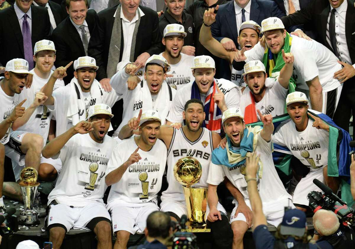 The San Antonio Spurs as they celebrate with the Larry O'Brien NBA championship trophy after the Spurs defeated the Miami Heat 107-84 in Game 5 of the NBA Finals June 14, 2014. Front row from left: MVP Kawhi Leonard, Tony Parker, Tim Duncan, Manu Ginobili and Patty Mills.