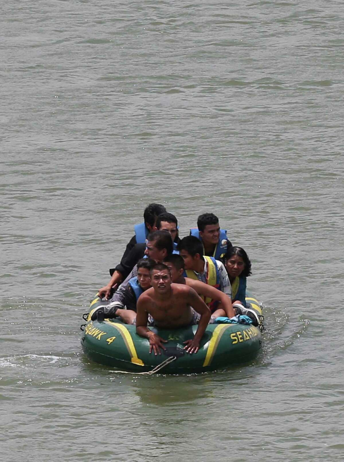 Using an inflatable raft, coyotes, or smugglers, move immigrants across the Rio Grande near the international bridge in Roma, Texas. A wave of Central American immigrant families and unaccompanied minors are entering the U.S. through the Rio Grande Valley south of Roma. This has caused law enforcement agencies to concentrate agents in the in that area. Higher risk smuggling operations have moved into Starr County in order to avoid the saturated border in Hidalgo, County.