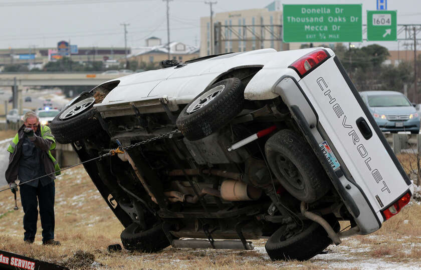 A wrecker driver uprights a pickup truck that rolled over on a bridge Thursday February 6, 2014 near