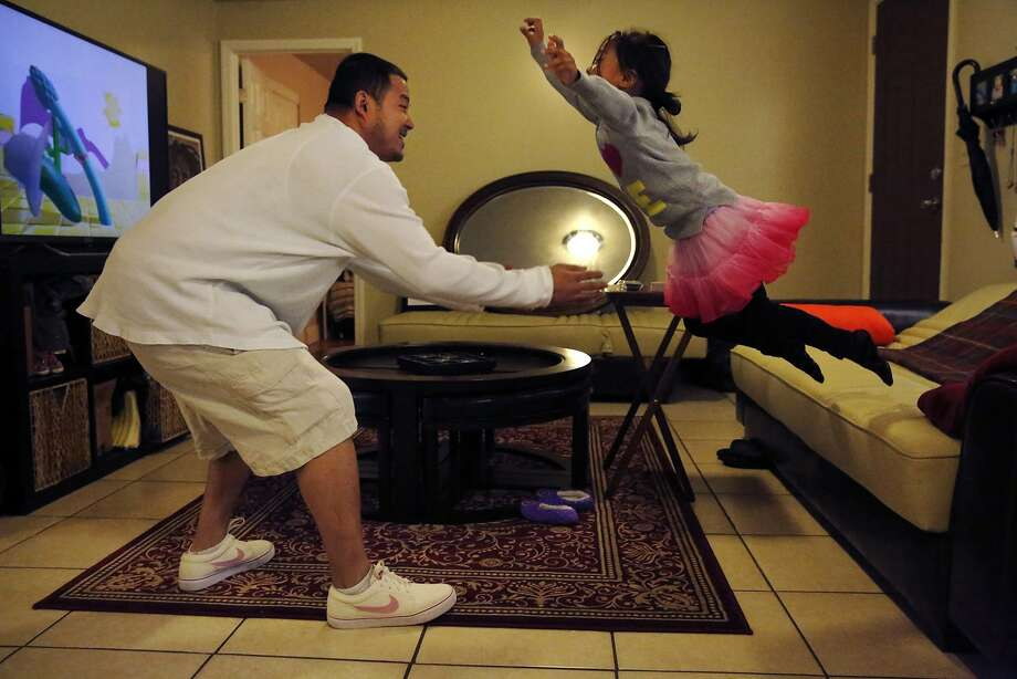 Nixon Matignas, 29, catches his daughter Divynity, 5, as she jumps off of a donated piece of furniture in his new apartment Dec. 23, 2014 in San Francisco, Calif. After doing one infantry tour in Iraq and medically retiring, Matignas also went through a divorce and eventually found himself on the streets. For a few years Matignas was homeless and battling PTSD. Last year he got a job at the VA and recently moved into a place of his own which he acquired through the Department of Housing and Urban Development Ð VA Supportive Housing (HUD-VASH) program. He can now have his daughter over to his place at least every other weekend and he is hoping to have her full-time (except weekends) starting next summer. Photo: Leah Millis, The Chronicle
