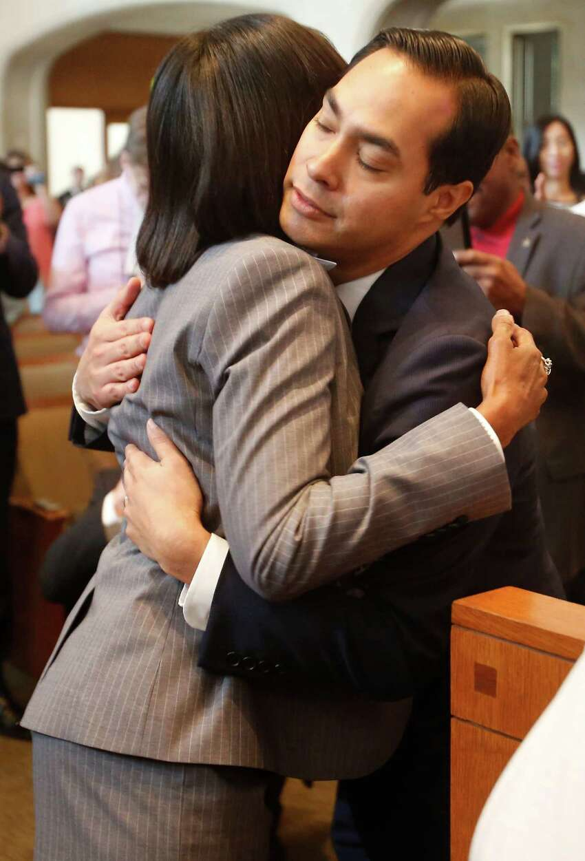 Incoming Mayor Ivy Taylor and outgoing Mayor Julian Castro embrace Tuesday July 22, 2014 in city council chambers after Castro submitted his resignation letter.