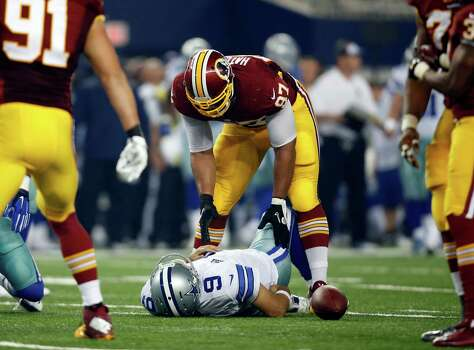 Washington Redskins' Jason Hatcher (97) checks on Dallas Cowboys quarterback Tony Romo (9) who lays on the ground injured after being sacked by the Redskins' Keenan Robinson during the second half on Oct. 27, 2014. Photo: Tim Sharp /Associated Press / FR62992 AP