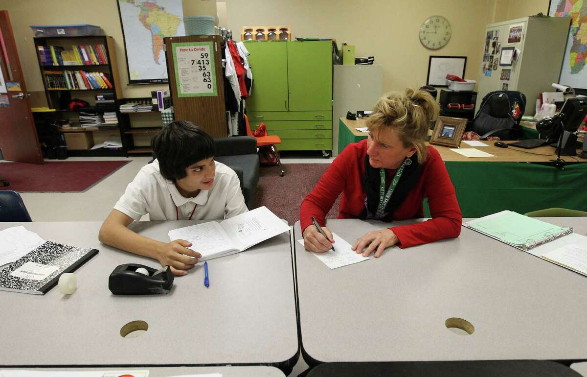 """Kitty Hawk Middle School teacher Theresa Beitel helps eighth-grade student Devon De La Garza with a language arts assignment on Tuesday, Dec. 16, 2014. De La Garza had a history of chronic behavior prior to educators trying restorative discipline. Beitel, who works closely with De La Garza, has seen the 14-year-old make great strides in class and in his behavior. The school will be using restorative discipline starting next year as an attempt to bridge relationships between students and educators to foster a more positive and productive learning environment. Despite not fully utilizing restorative discipline, school officials have already seen marked improvement with student behavior. """"Restorative discipline is the future,"""" Beitel said."""