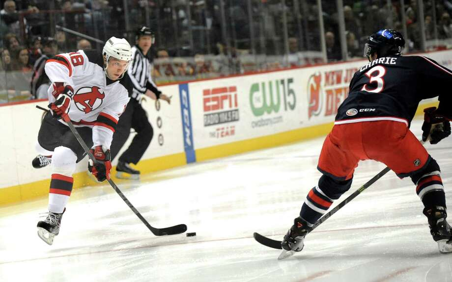 Devils' Stefan Matteau, left, fires a shot as Falcons' Hubert Labrie defends during their hockey game on Saturday, Dec. 27, 2014, at Times Union Center in Albany, N.Y. (Cindy Schultz / Times Union) Photo: Cindy Schultz / 00029286F