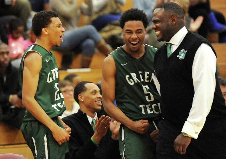 Green Tech coach Jamil Hood Sr., right, joins the bench as they react to a dunk during their game ag