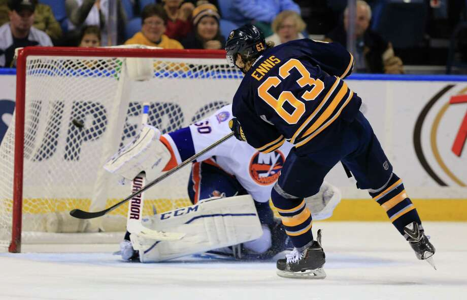 Buffalo Sabres Tyler Ennis (63) scores in the shootout against New York Islanders goaltender Kevin Poulin (60) during an NHL hockey game Saturday, Dec. 27, 2014, in Buffalo, N.Y. The Sabres won 4-3. (AP Photo/The Buffalo News, Harry Scull Jr.) ORG XMIT: NYBUE322 Photo: Harry Scull Jr. / The Buffalo News