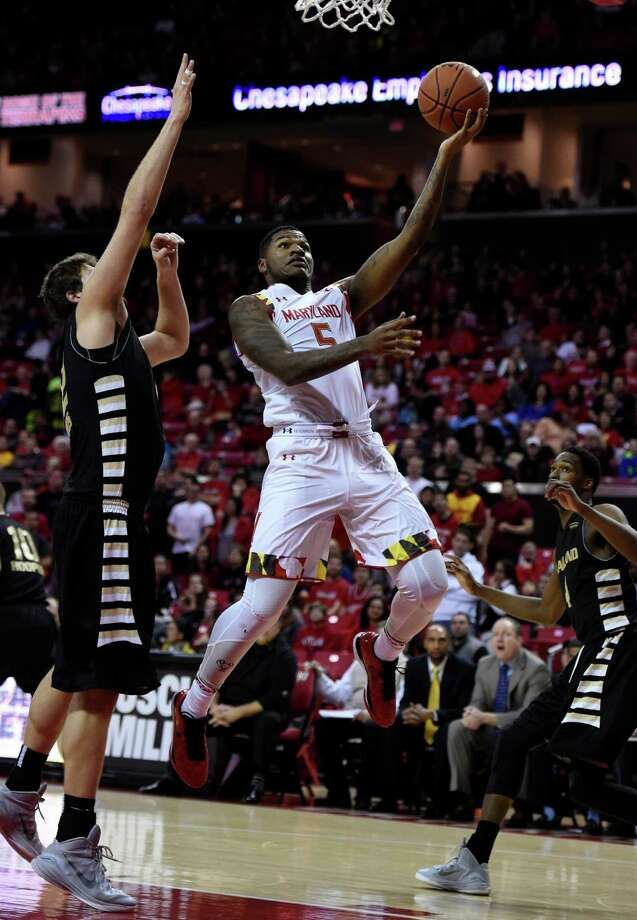 Maryland guard Dion Wiley (5) scores as Oakland center Corey Petros defends during the first half of an NCAA college basketball game Saturday, Dec. 27, 2014, in College Park, Md.(AP Photo/Gail Burton) ORG XMIT: MDGB102 Photo: Gail Burton / FR4095 AP