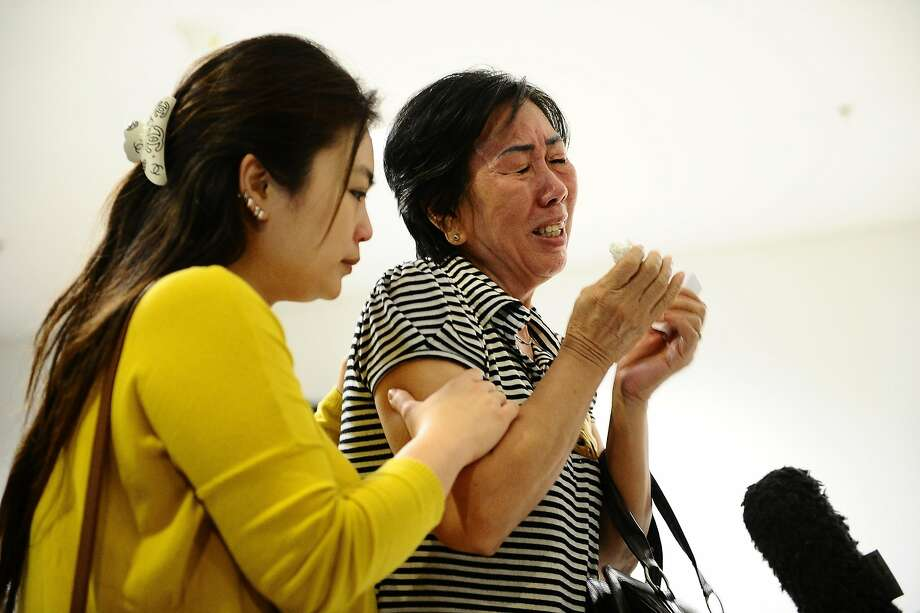 SURABAYA, INDONESIA - DECEMBER 28:  Relatives of missing Air Asia QZ8501 passengers cry at the crisis centre of Juanda International Airport Surabaya on December 28, 2014 in Surabaya, Indonesia. Air Asia announced the flight QZ8501 from Surabaya to Singapore, with 162 people on board, lost contact with air traffic control at 07:24 a.m. local time Sunday morning.  (Photo by Robertus Pudyanto/Getty Images) Photo: Robertus Pudyanto, Getty Images