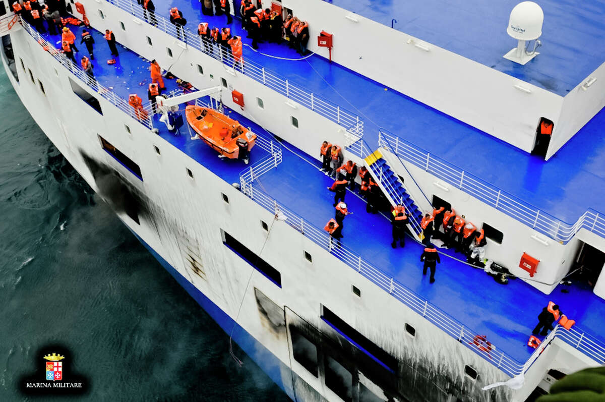 In this image released by the Italian Navy, passengers and crew are seen on the deck of the Italian-flagged ferry Norman Atlantic that caught fire in the Adriatic Sea, Sunday, Dec. 28, 2014. Italian and Greek rescue crews battled gale-force winds and massive waves as they struggled Sunday to evacuate hundreds of people from a ferry on fire and adrift in the channel between Italy and Albania. At least one person died and two were injured. The fire broke out before dawn Sunday on a car deck of the Italian-flagged Norman Atlantic, traveling from the western Greek port of Patras to the Italian port of Ancona on the Adriatic, with 422 passengers and 56 crew members on board.AP story: 1 dead, hundreds stranded in Greek ferry disaster
