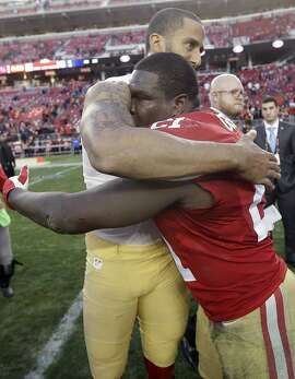 San Francisco 49ers quarterback Colin Kaepernick, left, hugs running back Frank Gore (21) after an NFL football game against the Arizona Cardinals in Santa Clara, Calif., Sunday, Dec. 28, 2014. The 49ers won 20-17. (AP Photo/Marcio Jose Sanchez)