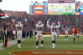 DENVER, CO - DECEMBER 28:  Cornerback Keith McGill #39, strong safety Brandian Ross #29, and cornerback D.J. Hayden #25 of the Oakland Raiders celebrate a touchdown against the Denver Broncos on a backward pass ruled a fumble that was recovered by McGill at Sports Authority Field at Mile High on December 28, 2014 in Denver, Colorado.  (Photo by Doug Pensinger/Getty Images)