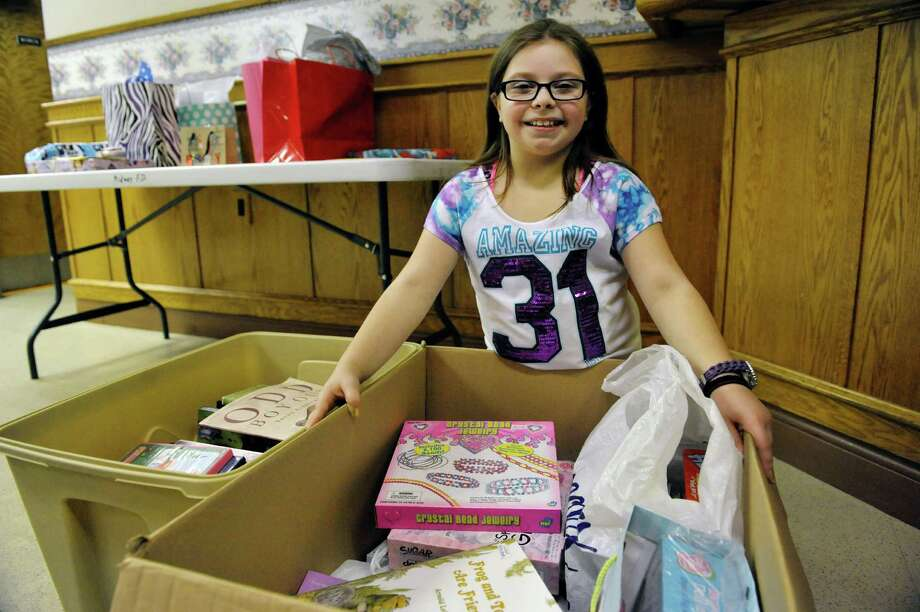 Alexis Hulett, 10, of Colonie poses with some of the childrenOs items guests brought to donate at her birthday party on Sunday, Dec. 28, 2014, in Colonie, N.Y.  Hulett back in 2008 started gathering donated items at her birthday to donate to different organizations after her her grandfather, Kenneth Coons, was injured in an accident.  Coons passed away in 2011after a battle with Leukemia.  Alexis and her family wanted to give back to the community while keeping the memory alive of her grandfather, whom she was very close to.  Last year Hulett collected over 200 books which were given to the Albany Tulip Queen's Literacy campaign.  This year childrenOs toys, books and movies are being collected to donate to the ChildrenOs Hospital at Albany Medical Center.   (Paul Buckowski / Times Union) Photo: Paul Buckowski / 00030002A