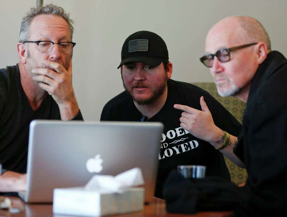 Iraq combat veteran Adan Olid, center, works on a song with songwriters Darden Smith, left, and Marshall Crenshaw during the Songwriting With Soldiers retreat at the Carey Institute for Global Good on Saturday, Nov. 15, 2014, in Rensselaerville, N.Y. Olid is one of more than 100 veterans who have turned their stories into sometimes affectingly personal songs at Songwriting With Soldiers retreats. (AP Photo/Mike Groll) ORG XMIT: NYMG201 Photo: Mike Groll / AP