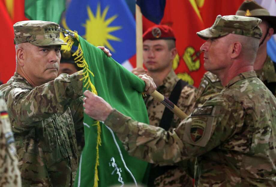 "Commander of the International Security Assistance Force (ISAF), Gen. John Campbell, left, and Command Sgt. Maj. Delbert Byers open the ""Resolute Support"" flag during a ceremony at the ISAF headquarters in Kabul, Afghanistan, Sunday, Dec. 28, 2014. The United States and NATO formally ended their war in Afghanistan on Sunday with the ceremony at their military headquarters in Kabul as the insurgency they fought for 13 years remains as ferocious and deadly as at any time since the 2001 invasion that unseated the Taliban regime following the Sept. 11 attacks. (AP Photo/Massoud Hossaini) ORG XMIT: MAH107 Photo: Massoud Hossaini / AP"