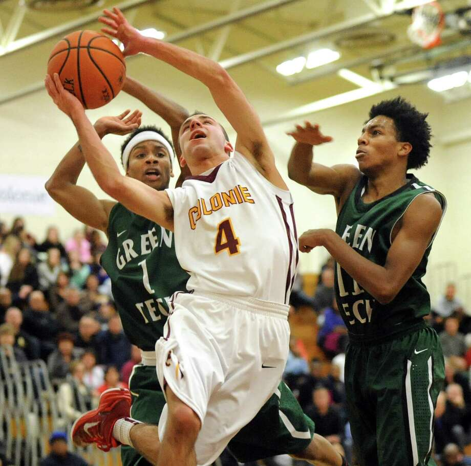 Colonie's Josh Paszkowski, center, goes to the hoop as Green Tech's Shakir John, left, and Naeem Pryor defend during their game in the Colonie Basketball Tournament final on Saturday, Dec. 27, 2014, at Colonie High in Colonie, N.Y. (Cindy Schultz / Times Union) Photo: Cindy Schultz / 00029996A