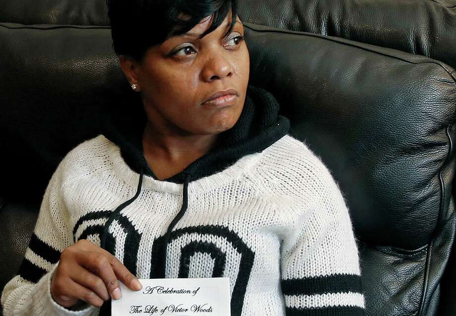 In this Dec. 11, 2014 photo, Terri Scroggins holds the memorial program for her fiance, Victor Woods, at her home in Boston's Dorchester neighborhood. Woods, who had struggled with heroin addiction for years, was being held on a drug possession charge at New York City's Rikers Island jail when he began shaking violently and convulsing. He died hours later. What exactly killed him remains under investigation, as are inmate claims that both guards and medical workers took up to 20 minutes to start helping him. (AP Photo/Elise Amendola) ORG XMIT: MAEA505 Photo: Elise Amendola / AP