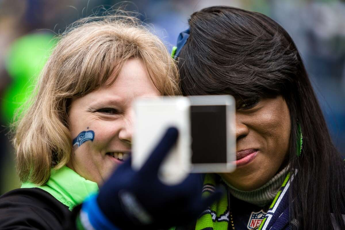 Beverly Sherman, right, mother of Richard Sherman, poses for a picture with fans before the first half of the final Seahawks regular season game Sunday, Dec. 28, 2014, at CenturyLink Field in Seattle, Washington. (Jordan Stead, seattlepi.com)