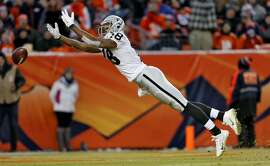 Oakland Raiders wide receiver Andre Holmes can't catch a pass during the second half of an NFL football game against the Denver Broncos, Sunday, Dec. 28, 2014, in Denver. (AP Photo/Joe Mahoney)