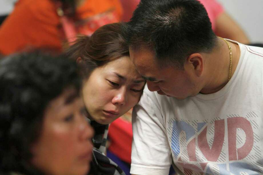 A relative of the passengers of AirAsia flight QZ8501 weeps as she waits for the latest news on the missing jetliner at a crisis center set up by local authority at Juanda International Airport in Surabaya, East Java, Indonesia, Sunday, Dec. 28, 2014.  A massive sea search was underway for an AirAsia plane that disappeared Sunday while flying from Indonesia to Singapore through airspace possibly thick with dense storm clouds, strong winds and lightning, officials said. (AP Photo/Trisnadi) ORG XMIT: XJAK109 Photo: Trisnadi / AP