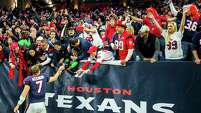Texans quarterback Case Keenum hands his wristbands to a fan as he takes a victory lap around the field on his way to the locker room after Sunday's game.